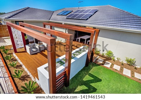 An aerial view of patio featuring wooden panel flooring and solar panels on the house roof #1419461543