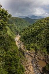An aerial view of the Barron river in its course between rainforest covered mountains.