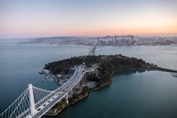 An aerial view of the Bay Bridge and Treasure Island with the City of San Francisco in the background.