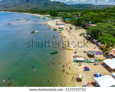 An aerial view of the busy coastline of Laiya, San Juan, Batangas with tourists enjoying the last days of summer in the Philippines #1125733712