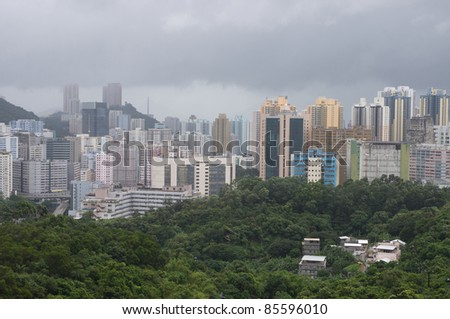 an aerial view of the cityscape of hong kong in the rain with fading layers of buildings