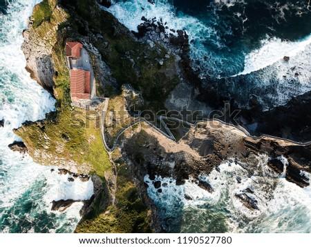 An aerial view of the Ermita de San Juan and the Escalinatas de Sanj Juan de Gaztelugatxe. Dramatic cliffs plunge into the north Atlantic ocean and a row of concrete steps zig zags up to the church.