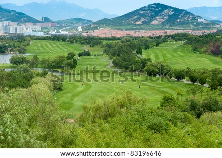 An aerial view of the fairway and green at a mountain resort golf course
