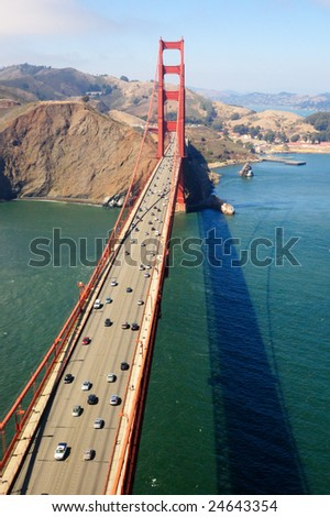 An aerial view of the Golden Gate Bridge on a sunny spring morning with Marin Headlands and Fort Baker in the background.