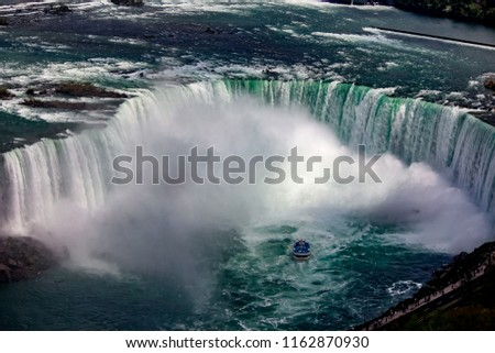 An aerial view of the Horseshoe Falls in from the Canadian side of Niagara Falls. A tour boat struggles in the wake of the falls and mist rises up. The water looks cold and dangerous. #1162870930