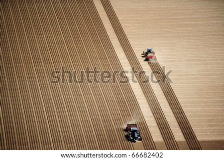An aerial view of 2 tractors planting potatoes in a field during the spring.