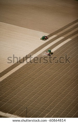 An aerial view of two tractors working in the field planting.  A great background image with a lot of area for copy.