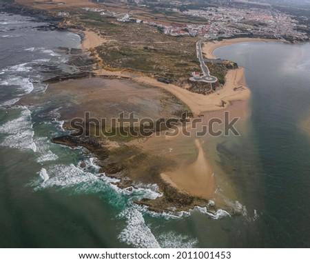 An aerial view of Vila Nova de Milfontes along Mira river with Praia do Farol in the foreground, Bej Сток-фото ©