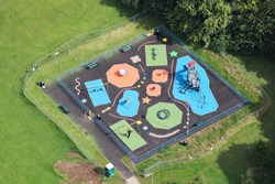 An aerial view taken from a helicopter of a colourful children's play area in a British outdoor park. It has been closed and fenced off because of the coronavirus pandemic.
