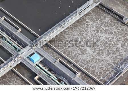 An aerial view taken from a helicopter of a large waste water and sewerage treatment plant in Wales. A view from above of  large concrete separations tanks full of foaming brown liquid. Stock photo ©