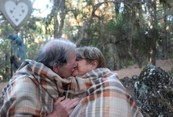 An affectionate kiss between two smiling elderly people in the woods. Around them many trees and a romantic wooden heart