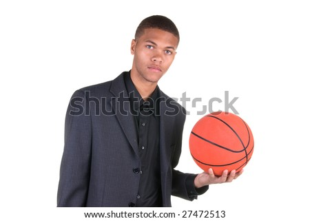 An African American basketball player holding a basketball while wearing his business casual suit