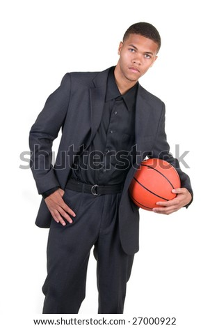 An African American basketball player poses in his business dress.