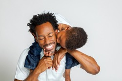 An African American boy on the shoulders of his father, leans over to kiss him on the cheek.  His father laughs with closed eyes.