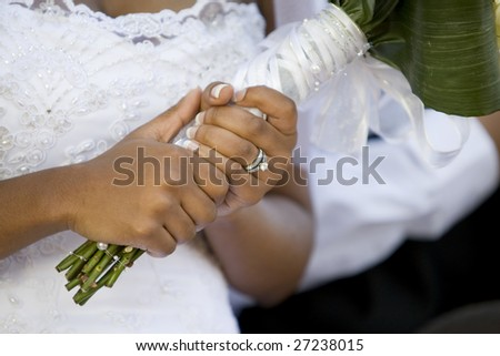 An African-American bride holding her bouquet after the wedding ceremony