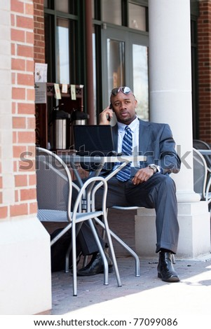 An African American business man in his early 30s talking on his cell phone and using his laptop or netbook computer.