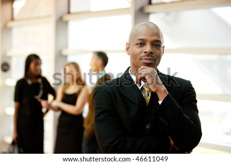 An African American business man with co-workers in the background
