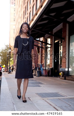 An African American business woman walking down the street