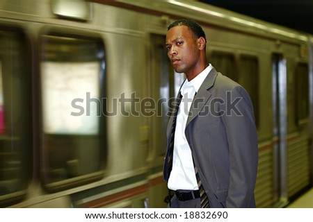 An African-American businessman awaits his commuter train