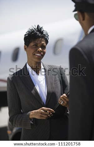 An African American businesswoman communicating with driver at airfield - stock photo