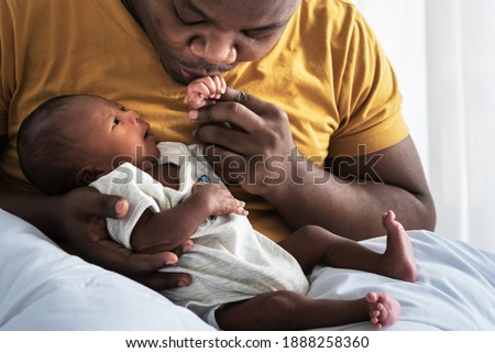 An African American father kissing hand,  his 12-day-old baby newborn son lying in bed in a white bedroom, with happy, concept to African American family and newborn
