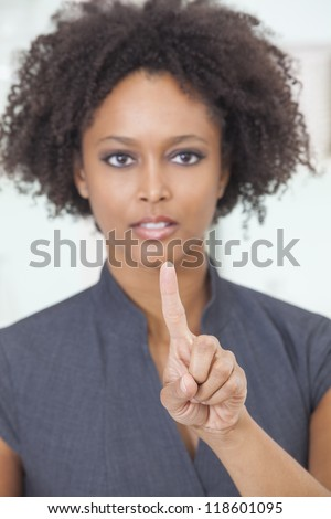 An African American female woman or businesswoman finger raised about to push a button or use a touchscreen touch a screen. The focus is on her finger.