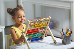 an african-american girl sits at a table and counts on an abacus and smiles