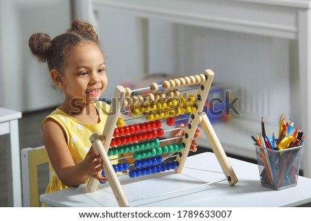 an african-american girl sits at a table and counts on an abacus and smiles Stockfoto ©