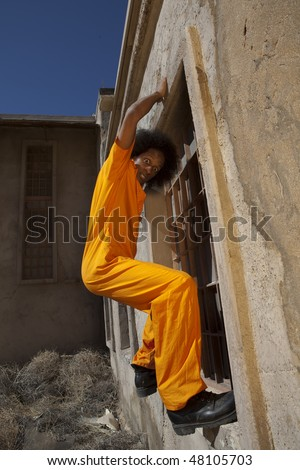 An african american male in orange prison coveralls escapes from prison by climbing a wall
