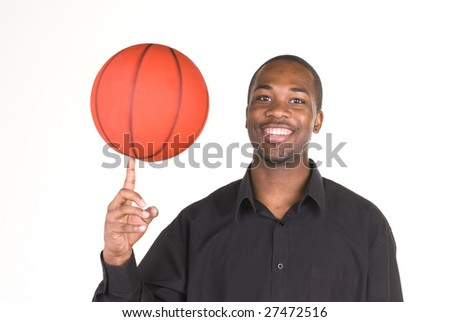 An African American man spins a basketball on his finger.