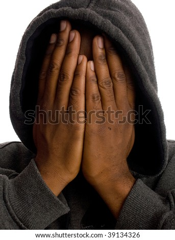 An African American man wearing a sweatshirt covers his face with his hands