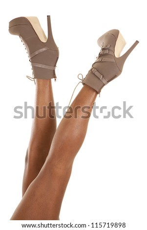 An African American's legs in her heeled boots showing some style. - stock photo