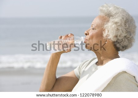 An African American senior woman drinking water from bottle with sea in the background