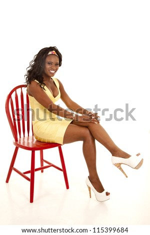 An African American sitting on a red chair in her yellow dress with a smile on her face.