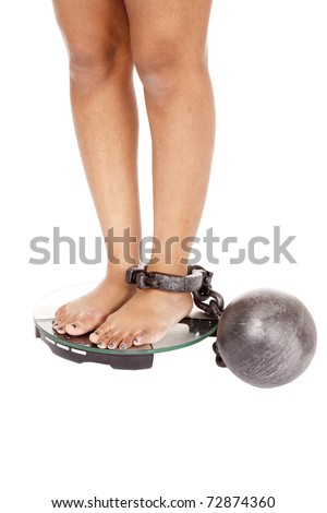 An African American woman has her legs in a ball and chain on the scales. - stock photo