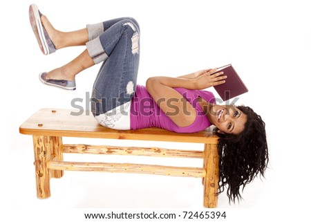 An African American woman is laying on a bench with a book.