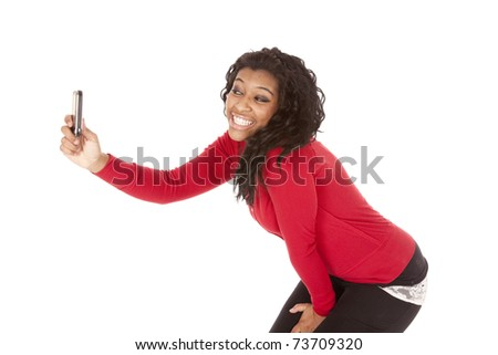 An African American woman is taking pictures of herself with her cell phone.
