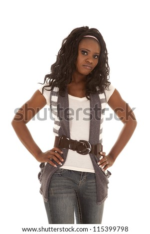 An African American woman standing in her cute clothes with her hands on her hips and a serious expression on her face.