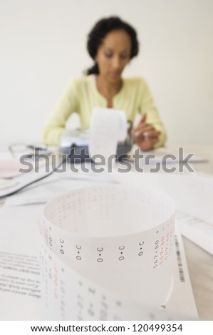An African American woman working on finances at home