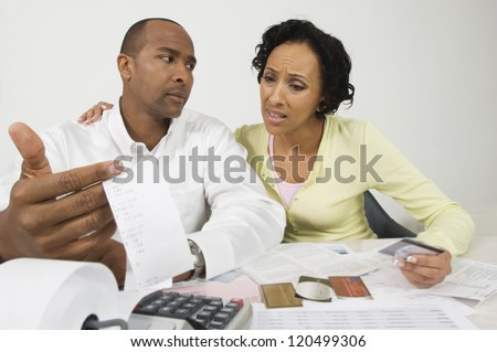 An African American worried couple with expense receipt and credit cards at home