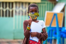 An African child wearing homemade mask for protection and giving a thumbs-up at school background - concept on students in face masks back to school in covid-19 pandemic season
