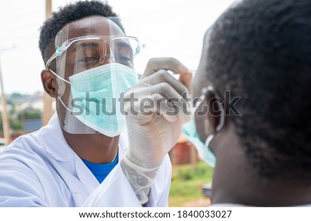 an african lab scientist taking nasal sample from a man