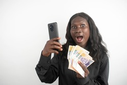 an african lady holding a phone and cash in her hands