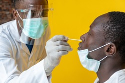 an african medical personnel taking nasal sample for covid-19 testing