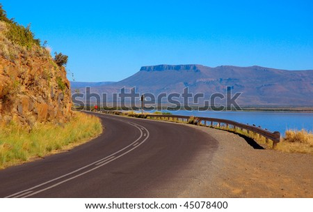 An African road around a table mountain close to a big lake