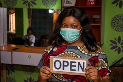 an african small business owner, makeup artist, holding a open sign in her store