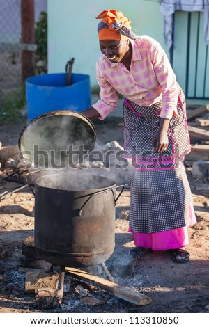 An african woman is making food the traditional way.