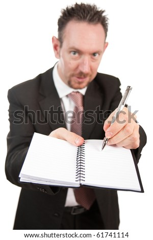 An aggressive looking businessman holds an open notebook and points at something on the book with his pen.  The pad is blank.  Differential focus on the pen and pad.
