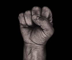 An aggressive monochrome adult male clenched fist isolated on a black background.