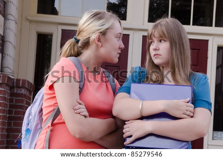 An aggressive teen girl intimidates another girl in front of their school, probably over a boy.